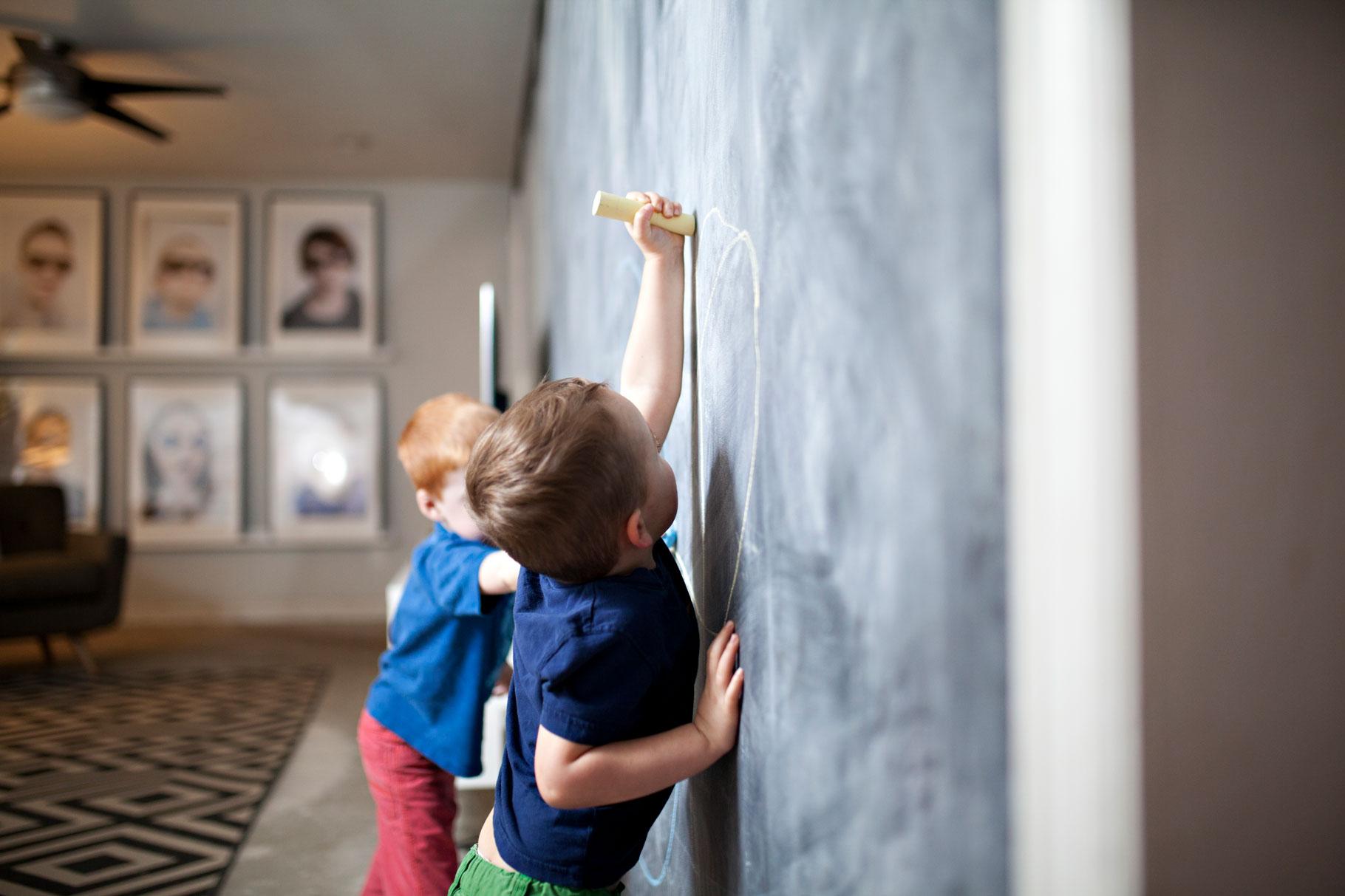 Des petits garçons dessinent sur un tableau géant