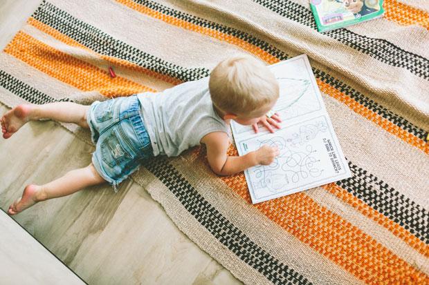 Petit enfant qui colorie sur un cahier allongé sur un tapis